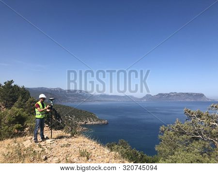 Geodetic Engineer Surveyor In White Hard Hat Doing Measurements With Gnss Satellite Receiver At The