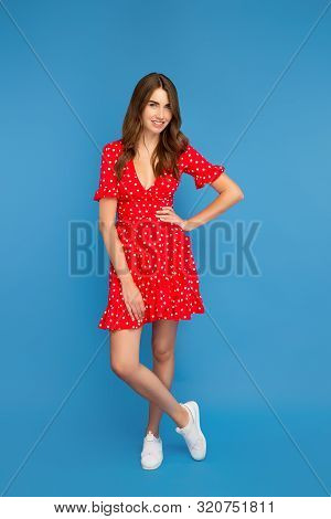 Full Lenght Photo Of Young Woman With Bright Smile In Red Dress Posing To Camera Over Blue Backgroun
