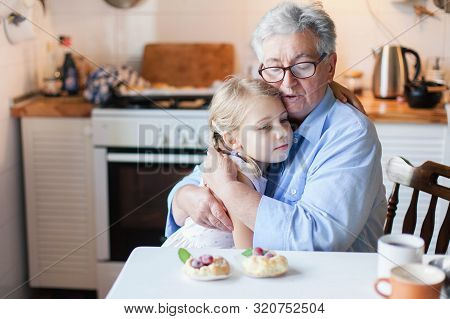 Senior Woman Is Hugging Child In Cozy Kitchen At Home. Kid Is Enjoying Kindness, Warm Hands, Care, S