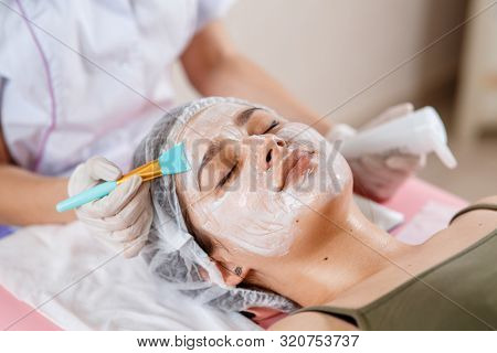Cosmetology Specialist Applying Facial Mask Using Brush, Making Skin Hydrated And Healthy. Attractiv