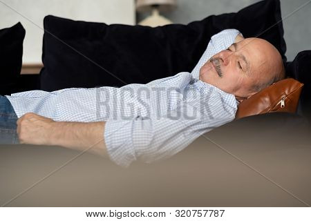 Tired Senior Hispanic Man Sleeping On Couch, Taking Afternoon Nap
