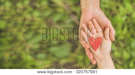 Childs Hand And Old Hand Grandmother. Concept Idea Of Love Family Protecting Children And Elderly Pe