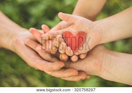 Childs Hand And Old Hand Grandmother Hold Heart. Concept Idea Of Love Family Protecting Children And