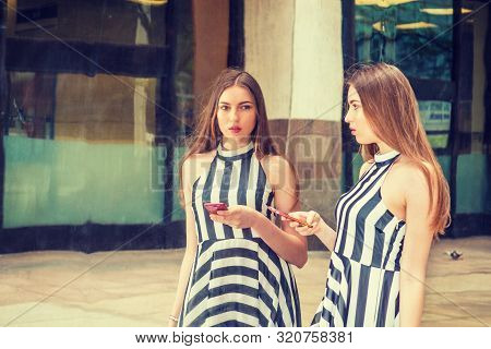Young Beautiful Woman Standing By Metal Mirror On Street, Holding Cell Phone, Looking At Reflections