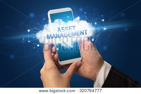 Female hand touching smartphone with ASSET MANAGEMENT inscription, cloud business concept