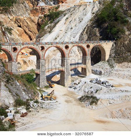White marble quarry old bridge and excavators at work. Apuan Alps Carrara Tuscany Italy Europe poster