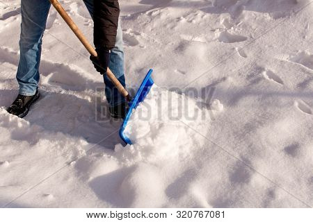 A Teenager Shoveling Snow In His Yard. The Concept Of A Snowy Winter