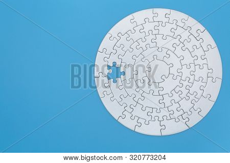 Unfinished White Jigsaw Puzzle Pieces On Blue Background, The Last Missing Piece Of The Jigsaw Puzzl