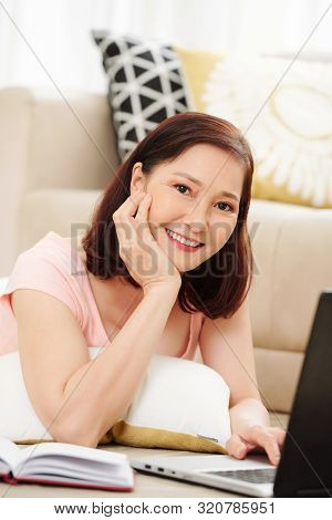 Positive Pretty Mature Asian Woman Lying On The Floor With Laptop And Looking At Camera