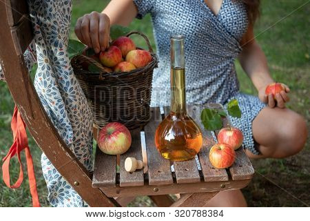 A Bottle Of Apple Cider Vinegar In A Garden, With A Woman In The Background