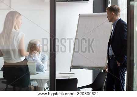 Diverse Colleagues Negotiate Discuss Whiteboard Presentation At Briefing