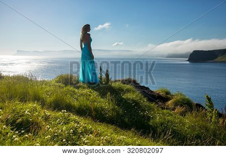 Pretty Long Haired Blonde Woman Stands In Long Turquoise Dress At The Top Of A Coastal Hill. Ireland