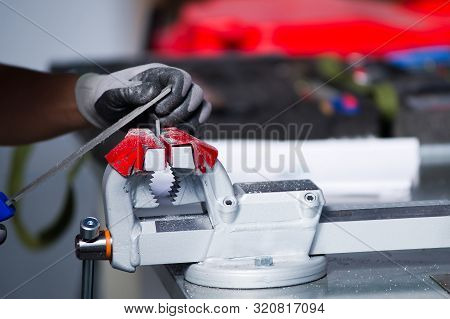 in the photo, a hand in a gray working glove is finalizing a metal workpiece clamped in a vice poster