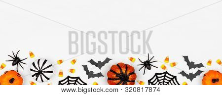 Halloween Bottom Border Banner Of Pumpkins, Candy And Decor. Flat Lay Over A White Background With C