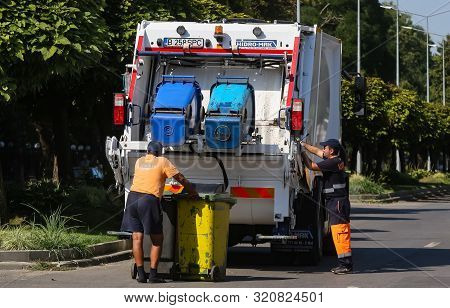 Bucharest, Romania - August 29, 2019: Two Sanitation Workers Empty The Trash Cans In A Garbage Car,