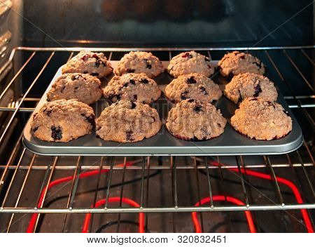 Muffin Pan With Blueberry Muffins In Hot Oven.