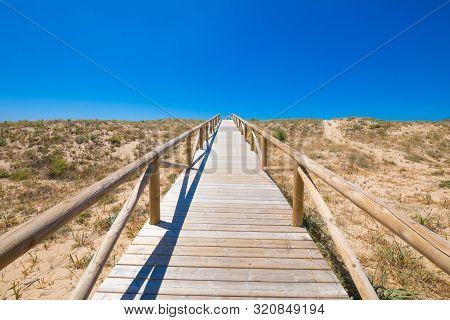 Wooden Planks Footbridge To The Blue Sky Horizon