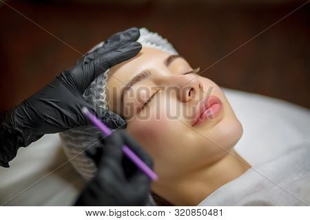 Permanent Make Up Eyeliner Procedure, Applying On Young Girl. Close-up. Young Beautiful Woman Making