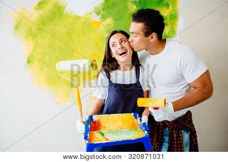 Young Multiethnic Couple Decorate Their New Home. Husband And Wife Are Painting The Wall With Roller