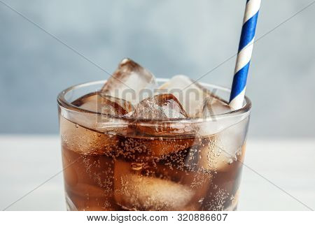 Glass Of Refreshing Soda Drink With Ice Cubes And Straw On Blue Background, Closeup