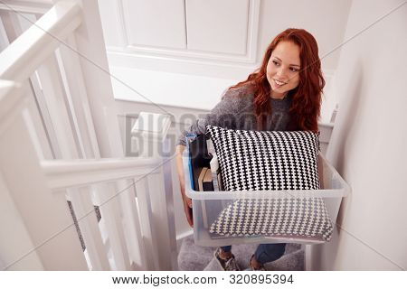Female College Student Carrying Box Up Stairs Moving Into Accommodation