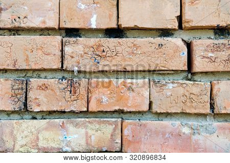 Fragment Of A Brick Wall Of 4 Lines Of Bricks, Roughly Laid Out With Heterogeneous Spots And Cracked
