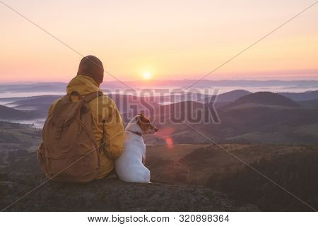 Alone tourist sitting on the edge of the cliff with dog against the backdrop of an incredible sunrise mountains landscape