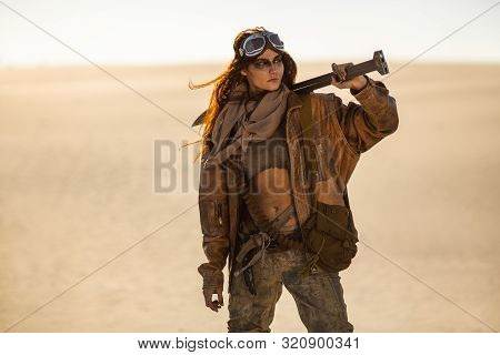 Post-apocalyptic Woman With Weapon Outdoors. Young Slim Girl Warrior In Shabby Clothes Holding Sword