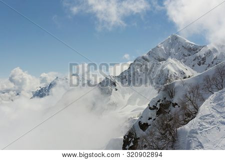 Winter mountain landscape and cloudy blue sky, Caucasus mountains.
