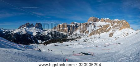 poster of Panorama of a ski resort piste with people skiing in Dolomites in Italy. Ski area Belvedere. Canazei, Italy