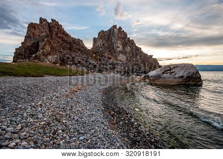 View From The Pebble Shore To The Rock Shamanka From The Island Of Olkhon On Lake Baikal. The Waves