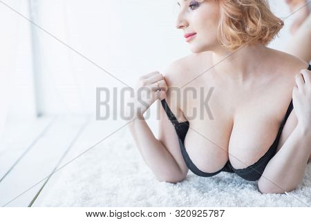 A European Girl With A Cute Face And Big Breasts In Black Underwear Lies On Her Stomach. Very Sexy.