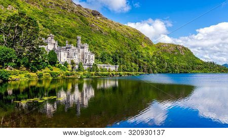 Kylemore Abbey, Beautiful Castle Like Abbey Reflected In Lake At The Foot Of A Mountain. Benedictine