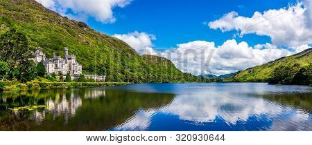 Panorama Of Kylemore Abbey, Beautiful Castle Like Abbey Reflected In Lake At The Foot Of A Mountain.