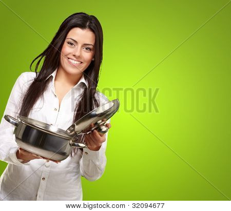 portrait of a young girl opening a sauce pan over a green background