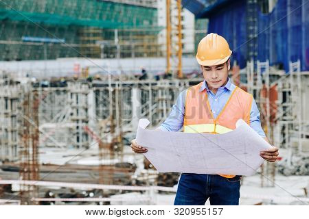 Serious Professional Asian Civil Engineer Examining Building Plan At Working Area