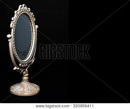 Vintage Oval Desk Mirror With White Frame On Black Background. Silver Rose Ornament