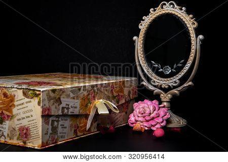 Vintage Oval Desk Mirror With White Frame, Potpourri Pieces And A Keepsake Box On Black Background