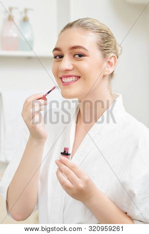 Portrait Of Happy Young Woman Applying Matte Mauve Liquid Lipstick When Doing Make-up
