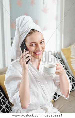 Happy Young Woman Talking On Phone And Drinking Coffee After Taking Morning Shower