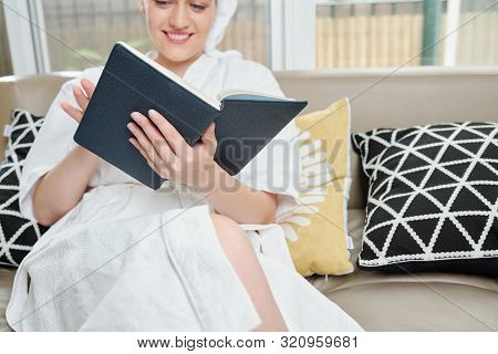 Relaxed Smiling Young Woman Reading A Book After Taking Bath At Home