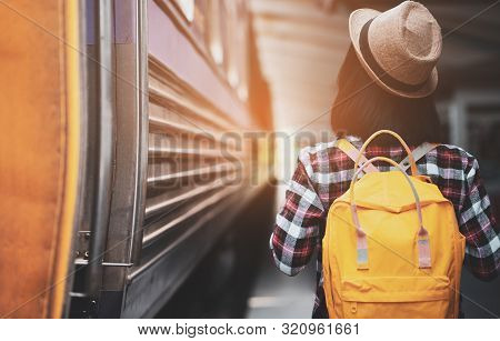 Young Asian Woman Traveler With Backpack In The Railway, Backpack And Hat At The Train Station With