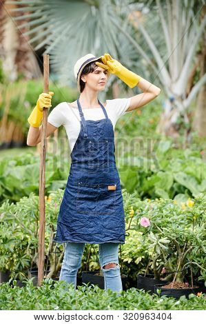 Tired Frowning Woman Wiping Sweat From Her Forehead After Planting Flowers In Garden All Day Long