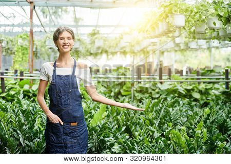Pretty Young Woman With Short Hair Making Hand Gesture To Show Her Greenhouse Full Of Various Plants