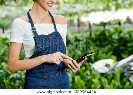 Cropped Image Of Nursery Garden Manager Using Nfs Device Attached To Smartphone When Entering Sum Of