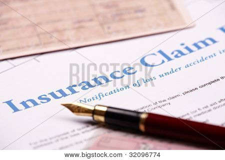Blank insurance claim form and other papers like ID or vehicle documents and pen lying on desk poster