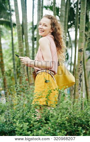 Pretty Young Laughing Woman With Smartphone In Hands Spending Time In City Flower Graden