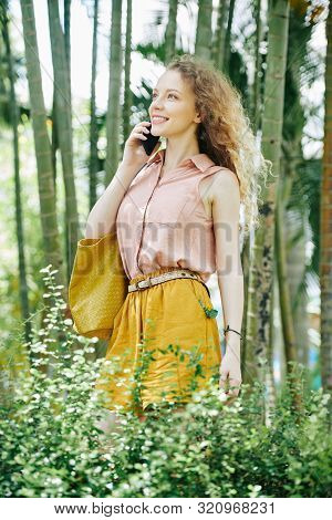 Portrait Of Happy Inspired Young Woman Standing In Summer Park And Talking On Phone With Friend