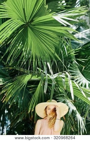 Beautiful Young Happy Woman In Straw Hat Standing Under Palm Tree On Summer Day