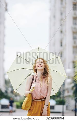 Happy Emotional Young Woman With Blond Curly Hair Walking In The Street With Big Umbrella And Lookin